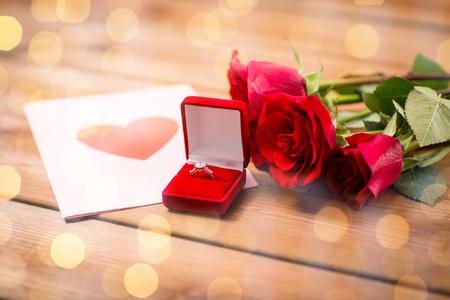 uprzejmości: miłość, propozycja, Walentynki i święta pojęcie - zamknąć pudełko z pierścionek zaręczynowy diament, czerwonych róż i życzeniami na drewnie Zdjęcie Seryjne