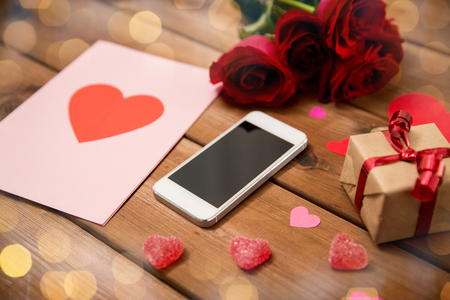 uprzejmości: romance, valentines day and holidays concept - close up of smartphone, gift box, red roses and greeting card with heart-shaped candies on wood