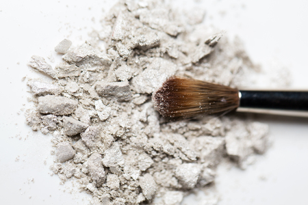 cosmetics, makeup and beauty concept - close up of makeup brush and eyeshadow