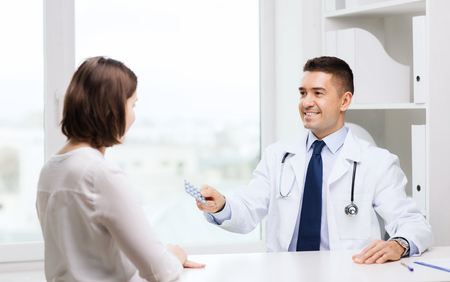 doctor giving pills: medicine, health care, medication and people concept - smiling doctor with clipboard giving pills to young woman at hospital