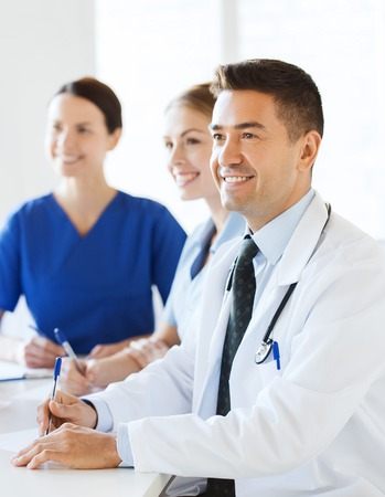 hospital, profession, medical education, people and medicine concept - group of happy doctors meeting on presentation at hospital Stock Photo