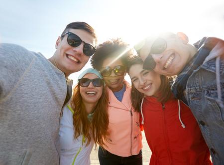 grupo de personas: turismo, viaje, gente, ocio y concepto de la tecnología - grupo de amigos sonrientes adolescentes que están tomando autofoto aire libre Foto de archivo