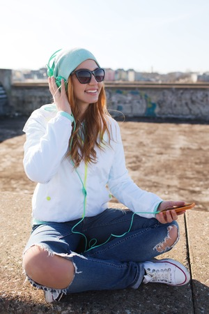 young happy couple: technology, lifestyle and people concept - smiling young woman or teenage girl with smartphone and headphones listening to music outdoors