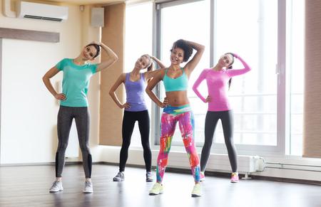 피트 니스, 스포츠, 교육, 체육관 및 라이프 스타일 개념 - 밖으로 작동 하 고 체육관에서 스트레칭 행복 한 여자의 그룹