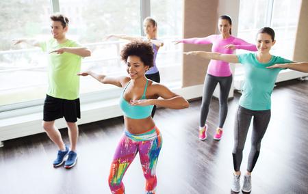 baile latino: fitness, deporte, la danza y el estilo de vida concepto - grupo de gente sonriente con zumba baile entrenador en el gimnasio o estudio