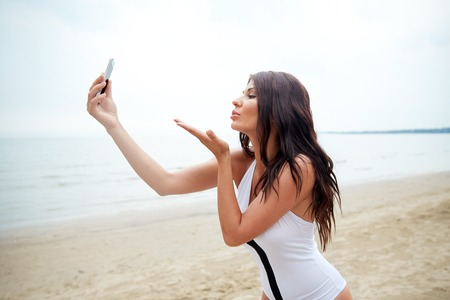 sexy pictures: summer, travel, technology and people concept - sexy young woman taking selfie with smartphone and sending blow kiss on beach