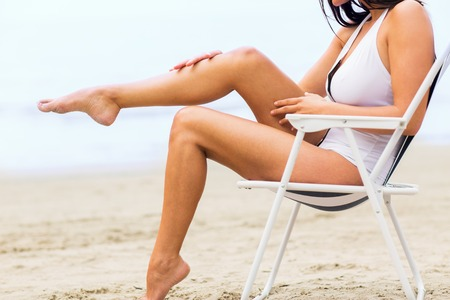 girl legs: summer vacation, tourism, travel, holidays and people concept - close up of woman sunbathing in lounge on beach Stock Photo
