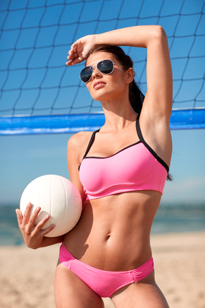 summer vacation, sport and people concept - young woman with volleyball ball and net on beach
