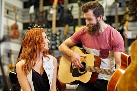 boyfriends: music, sale, people, musical instruments and entertainment concept - happy couple of musicians with guitar at music store