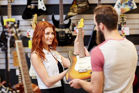 parejas felices: m�sica, venta, gente, instrumentos musicales y concepto de entretenimiento - asistente femenina que muestran la guitarra el�ctrica a los clientes en la tienda de m�sica