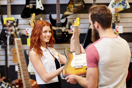 happy customer: music, sale, people, musical instruments and entertainment concept - female assistant showing electric guitar to customer at music store Stock Photo