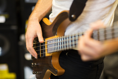 entertainment concept: music, people, musical instruments and entertainment concept - close up of musician with guitar at music studio