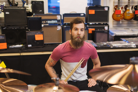 cymbals: music, sale, people, musical instruments and entertainment concept - male musician at drum kit cymbals in music store