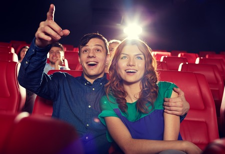 at the theater: cinema, entertainment, gesture, emotions and people concept - happy friends watching movie pointing finger to screen in theater Stock Photo
