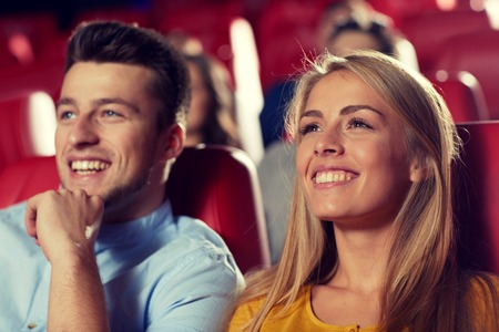 movie theatre: cinema, entertainment and people concept - happy friends watching movie in theater