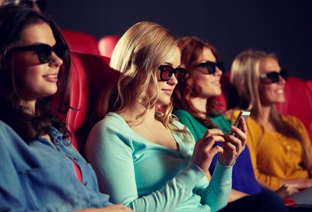 at the theater: cinema, technology, entertainment and people concept - happy woman with 3d glasses and smartphone reading message in movie theater