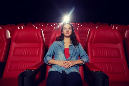 empty of people: cinema, entertainment and people concept - young woman watching movie alone in empty theater auditorium Stock Photo