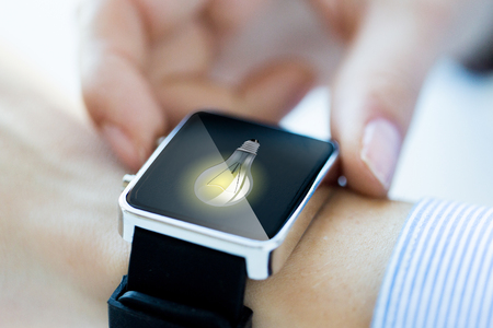close icon: business, technology, communication, conection and people concept - close up of woman hands with lightbulb icon on smartwatch screen Stock Photo