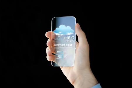 technology, application, weather, forecast and people concept - close up of male hand holding and showing transparent smartphone with cloud icon and air temperature on screen over black background