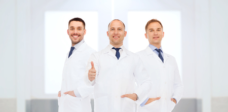 showing: healthcare, profession, people, gesture and medicine concept - group of happy male doctors at hospital showing thumbs up