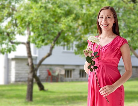 trimester: pregnancy, motherhood, people, holidays and expectation concept - happy pregnant woman with white rose flower over home yard or garden background