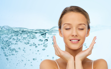 limpieza de cutis: belleza, gente, cuidado de la piel y el concepto de salud - joven cara y las manos sonriendo sobre las salpicaduras de agua sobre fondo azul