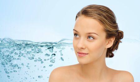 美容、保湿、肌のケアと健康のコンセプト - 水スプラッシュ背景の上の若い女性の顔や肩に笑みを浮かべて人