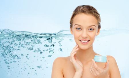 oxigeno: belleza, gente, cosméticos, cuidado de la piel y cosméticos concepto - mujer joven feliz que aplica la crema a la cara sobre las salpicaduras de agua sobre fondo azul Foto de archivo