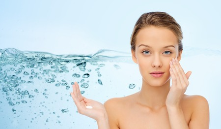 beauty, people, moisturizing cosmetics, skin care and health concept - young woman applying cream to her face over water splash background