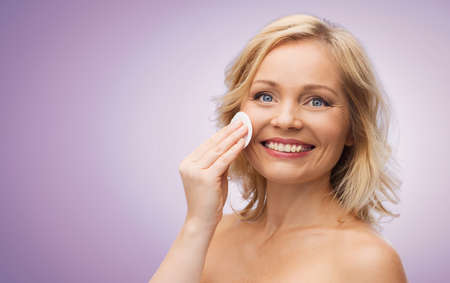 removing make up: beauty, people and skincare concept - happy middle aged woman cleaning face and removing make up with cotton pad over violet background
