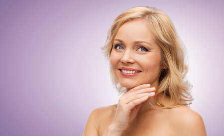 touching face: beauty, people and skincare concept - smiling middle aged woman with bare shoulders touching face over violet background Stock Photo
