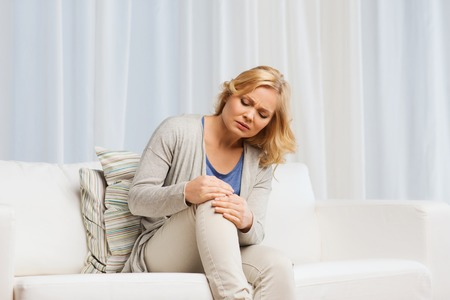 people, healthcare and problem concept - unhappy woman suffering from pain in leg at home Stock Photo