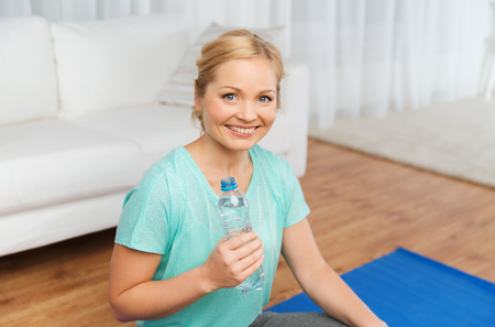 weight room: fitness, sport, people and healthy lifestyle concept - happy woman with bottle of water after exercising on mat at home Stock Photo