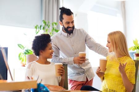 negocios, comunicación, bebidas, puesta en marcha y el concepto de la gente - feliz equipo creativo beber café y hablando de algo en la oficina