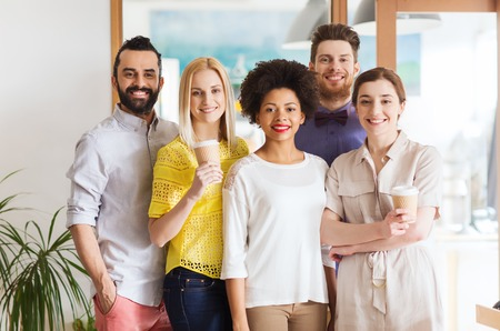 bedrijf, opstarten, mensen, drankjes en teamwork concept - gelukkig lachend internationale creatieve team met wegwerp papieren koffiebekers in kantoor Stockfoto