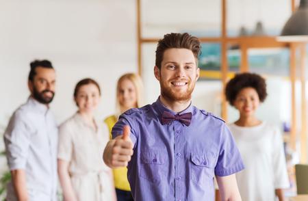 ビジネス ・ スタートアップ、人々、ジェスチャーとチームワークの概念 - ひげと蝶ネクタイを示す幸せな若い男の親指をオフィスの創造的なチーム