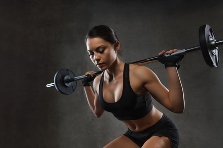 sport, fitness, bodybuilding, weightlifting and people concept - young woman with barbell flexing muscles in gym Stock Photo