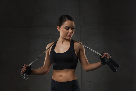 fitness training: sport, fitness, training, stamina and people concept - young sporty woman with jumping rope