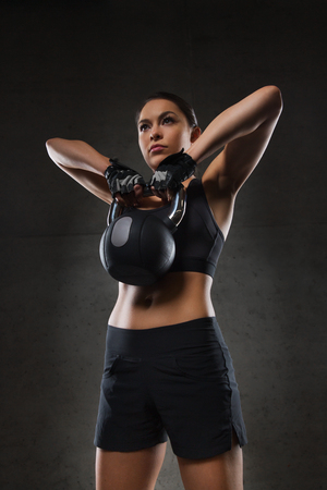 in a row: fitness, sport, exercising, weightlifting and people concept - young woman flexing muscles with kettlebell in gym