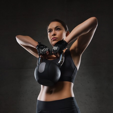 kettlebell: fitness, sport, exercising, weightlifting and people concept - young woman flexing muscles with kettlebell in gym