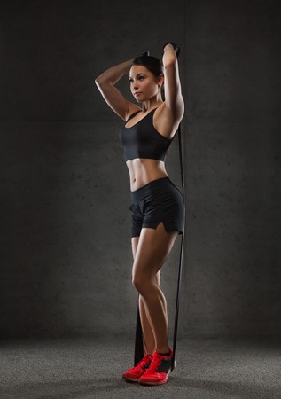 pull up: fitness, sport, training, people and lifestyle concept - woman doing exercises with expander or resistance band in gym