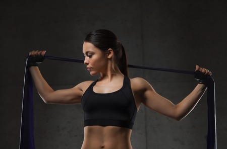 pull up: fitness, sport, training, people and lifestyle concept - woman doing exercises with expander in gym