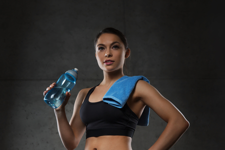 water sport: fitness, sport, training, drink and lifestyle concept - woman with towel drinking water from bottle in gym