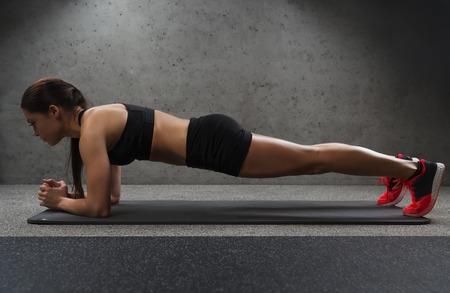 condición física, el deporte, la formación y las personas concepto - mujer que hace ejercicio tablón en colchoneta en el gimnasio