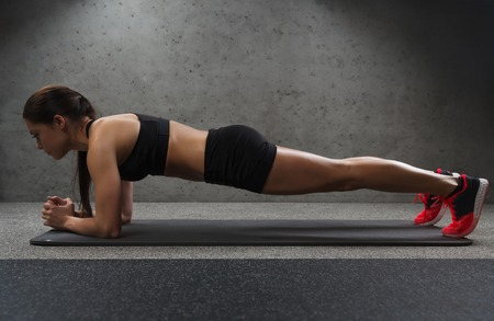 plank: fitness, sport, training and people concept - woman doing plank exercise on mat in gym Stock Photo