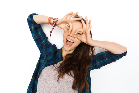making face: people and teens concept - happy smiling pretty teenage girl making face and having fun