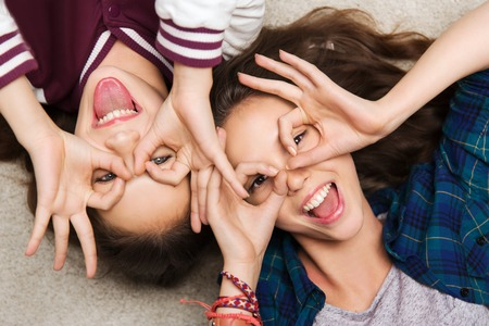 making face: people, friends, teens and friendship concept - happy smiling pretty teenage girls having fun and making faces Stock Photo
