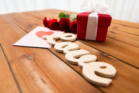 attentions: love,  romance, valentines day and holidays concept - close up of gift box, red roses and greeting card with heart on wood