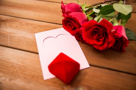uprzejmości: love,  romance, valentines day and holidays concept - close up of gift box, red roses and greeting card with heart on wood