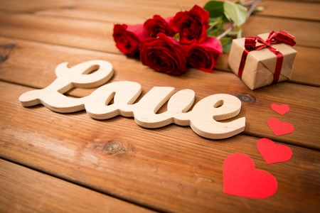 attentions: love, romance, valentines day and holidays concept - close up of gift box, red roses and hearts on wood Stock Photo